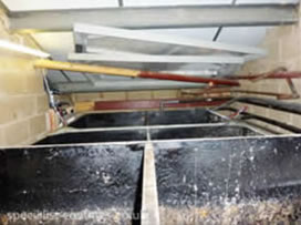 Cold water storage tanks located in cramped attic void.